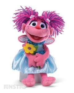 The lovable and huggable Abby Cadabby doll from the Sesame Street GUND plushy collection is holding a yellow flower, and will surely brighten any day!